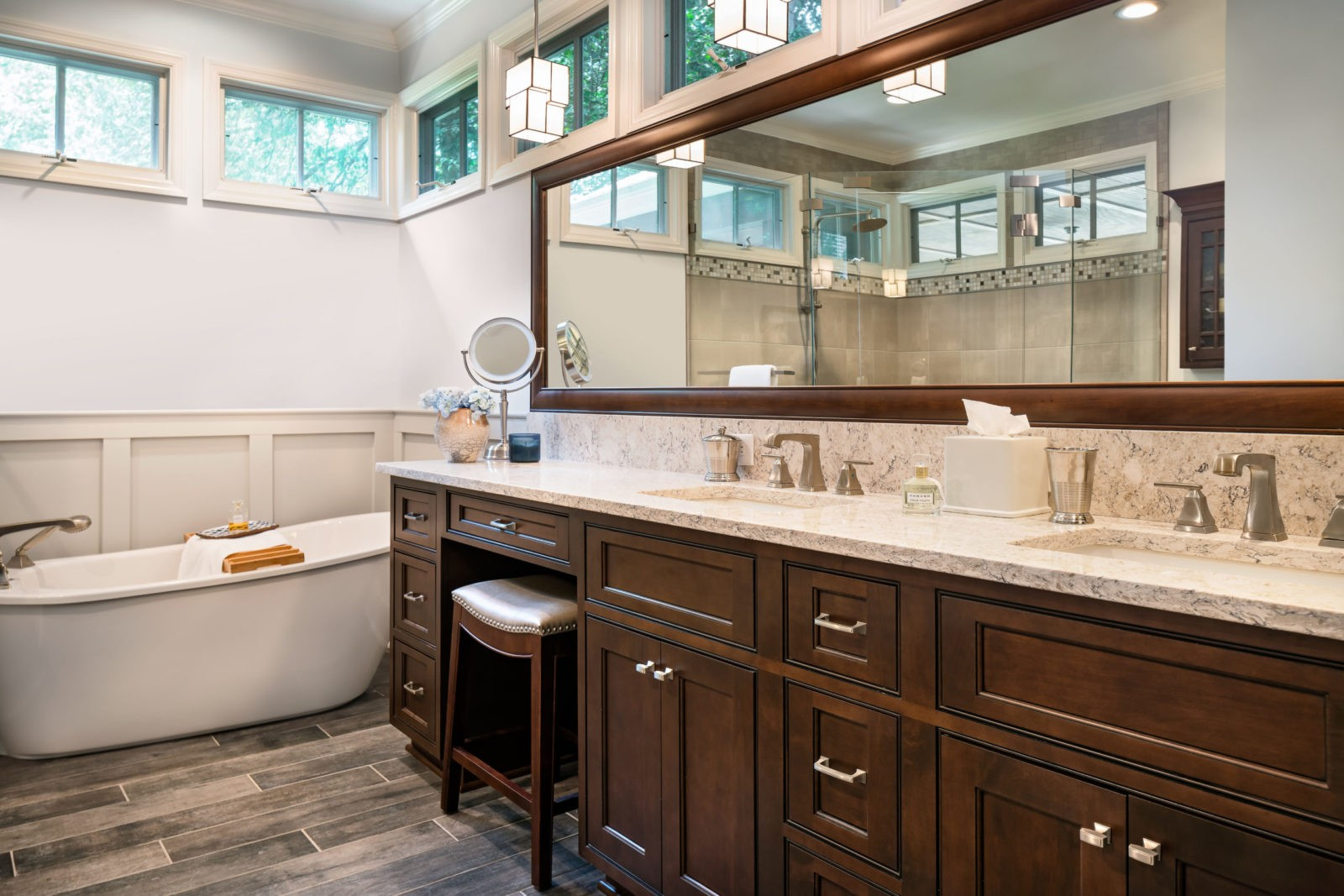 """Creamy quartz countertops with a 6"""" high backsplash rest on top of stained, inset cabinetry in the Craftsman master bathroom remode"""