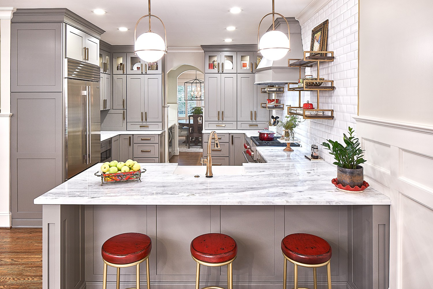 White and gray marble countertops contrast with the dovetail gray cabinetry. Red stools and accessories offer a pop of color.