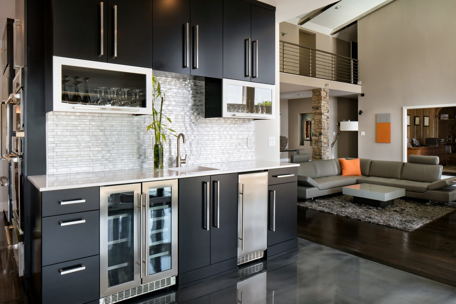 Modern wet bar with black cabinets and ice maker