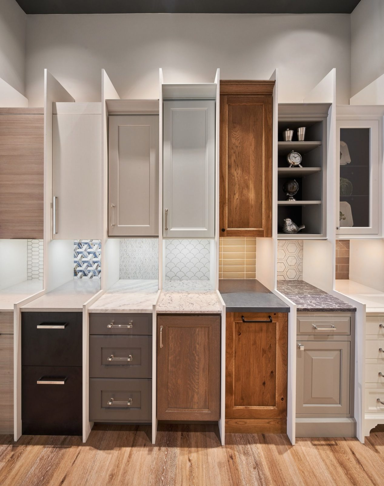 Miniature kitchen cabinet display with various door styles and finishes.